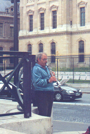 Man playing clarinet near the Lourve