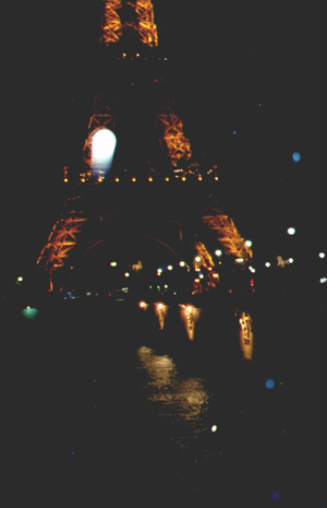 The Eiffel Tower at night and in a downpour of rain.